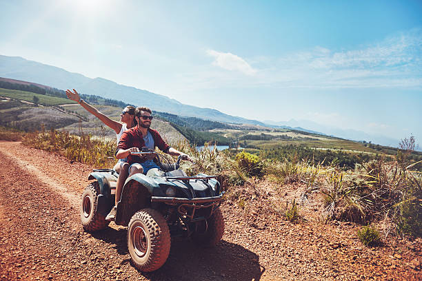 Couple on an off road adventure Young couple on an off road adventure. Man driving quad bike with girlfriend sitting behind and enjoying the ride in nature. quadbike stock pictures, royalty-free photos & images