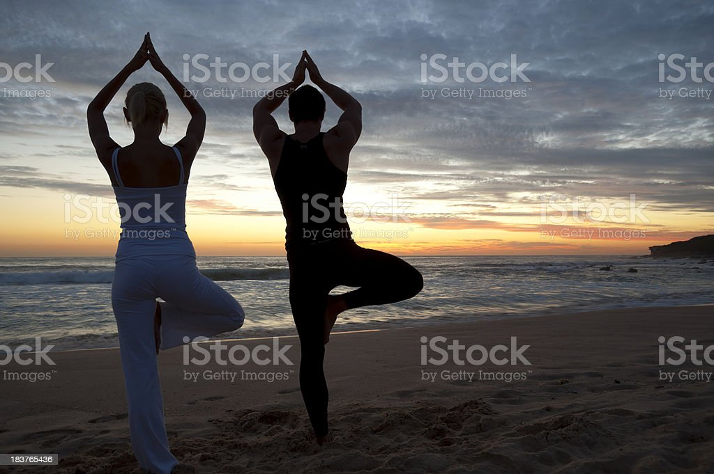Couple on beach at sunset  in yoga position royalty-free stock photo