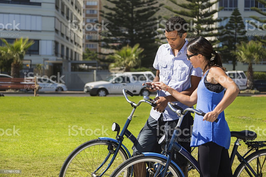 Couple on Bicycles Check Mobile Phone stock photo