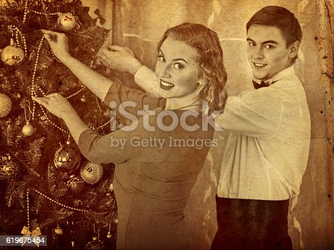 Old photo of loving couple preparing party near Christmas tree. Black and white retro picture.