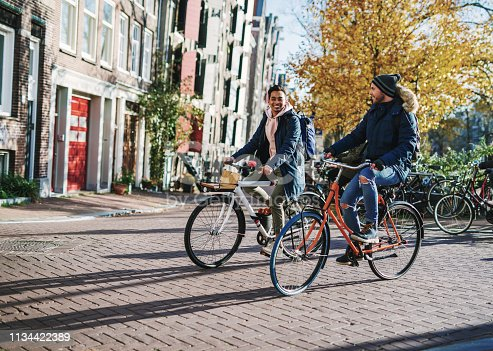Modern gay couple enjoying the city break in late autumn or early winter in sunny Amsterdam