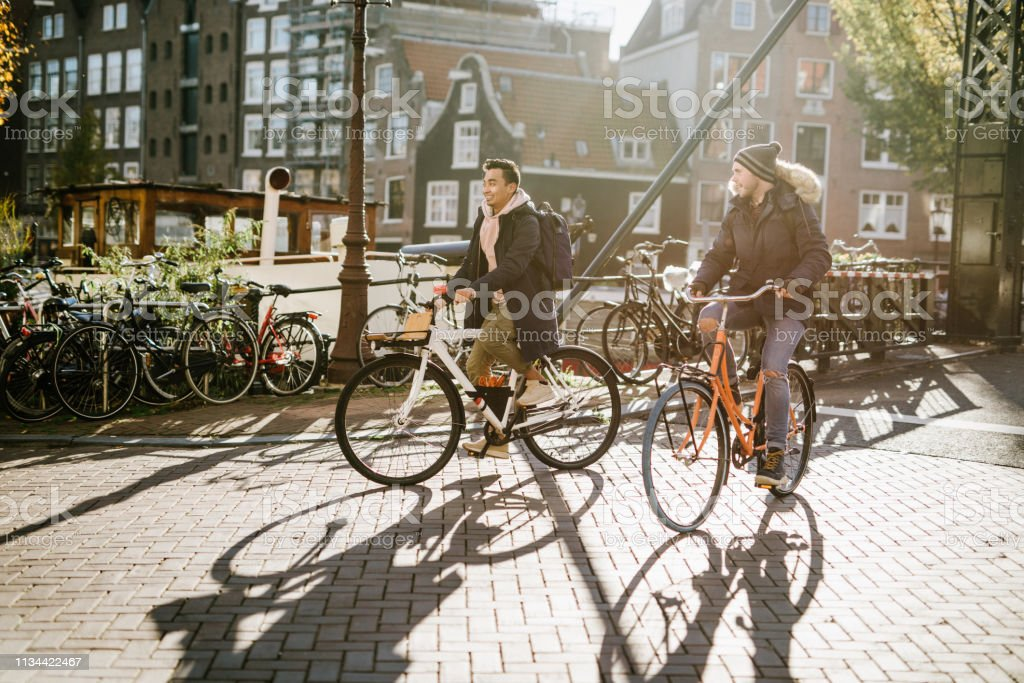 LGBT couple on city break - diverse millennial gay guys are in relationship and spending time on city break Modern gay couple enjoying the city break in late autumn or early winter in sunny Amsterdam 20-24 Years Stock Photo