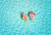 A happy vacation couple in swimsuits enjoys the tropical sun of the Maldives on colorful floats over turquoise colored sea