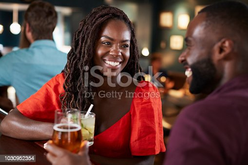 Couple On Date Sitting At Bar Counter And Talking