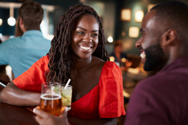 Couple On Date Sitting At Bar Counter And Talking Couple On Date Sitting At Bar Counter And Talking date stock pictures, royalty-free photos & images