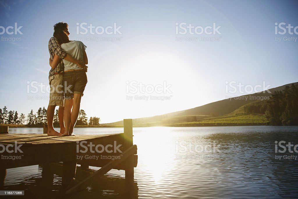 Couple on dock hugging and watching sun set over lake stock photo