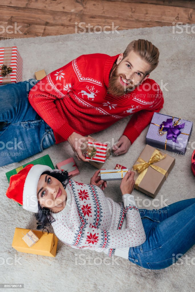 couple on floor with christmas gifts stock photo