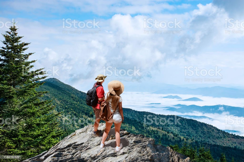 Couple on hiking trip, standing on top of the mountain over the clouds. stock photo