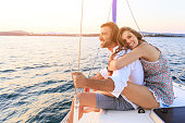 Couple on honeymoon traveling with yacht. Woman sitting behind the man and hugging him. Both with casual clothes.