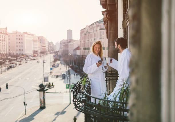 couple on hotel balcony - accappatoio foto e immagini stock