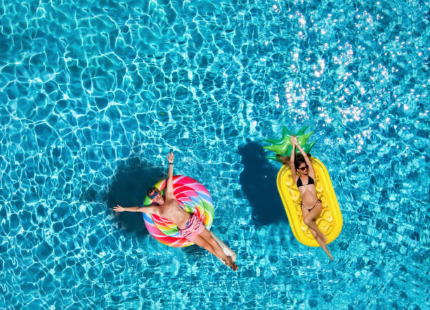 Couple on inflatable floats over blue pool water stock photo