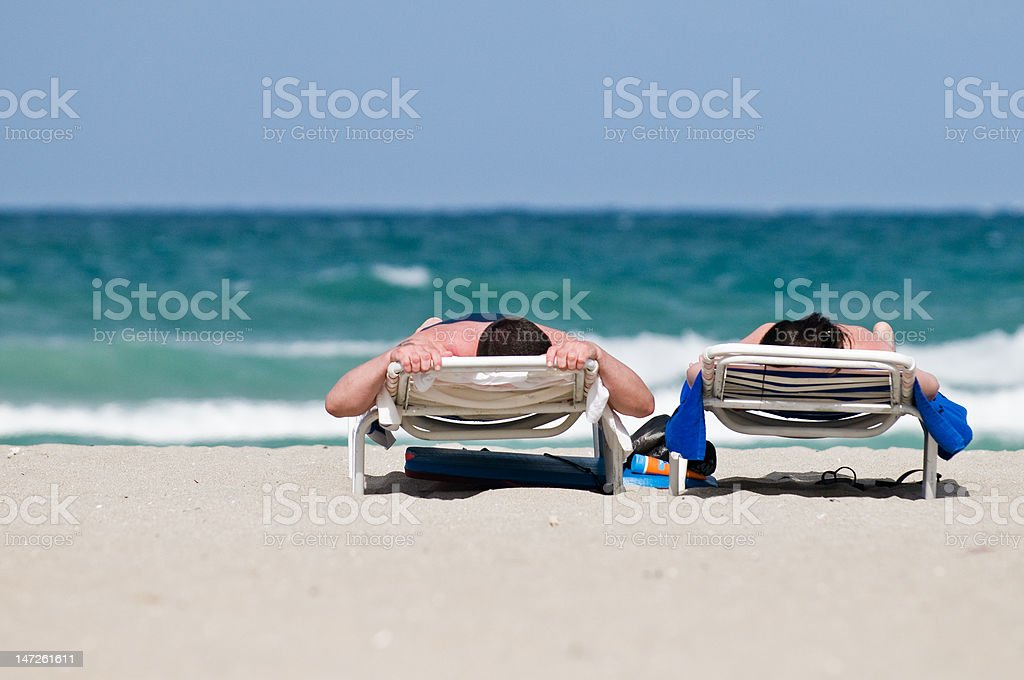 Couple on Lounge Chairs at Beach stock photo