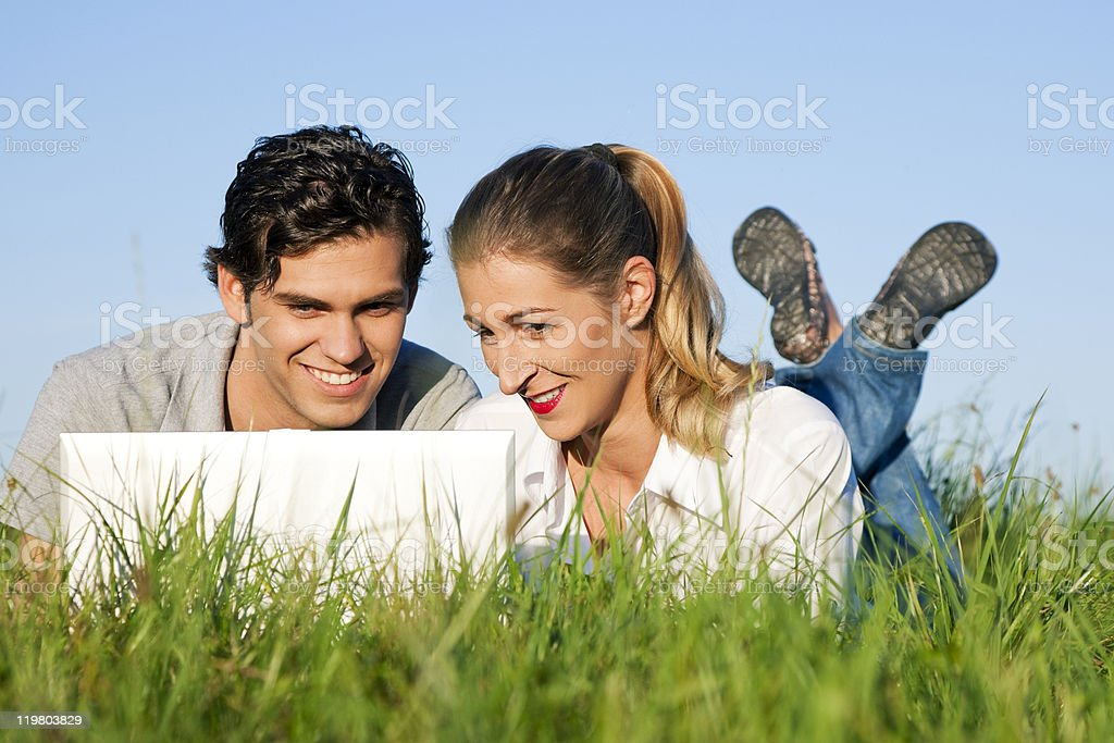 Couple on meadow using wi-fi for Internet royalty-free stock photo