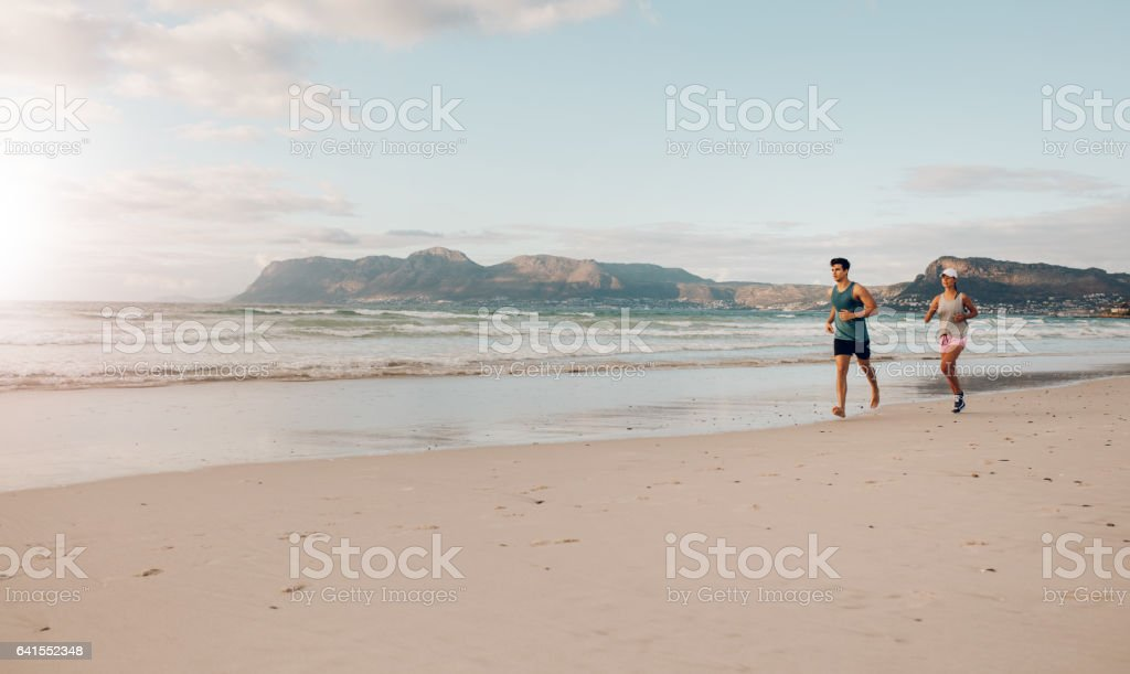 Couple on morning run at the beach – Foto
