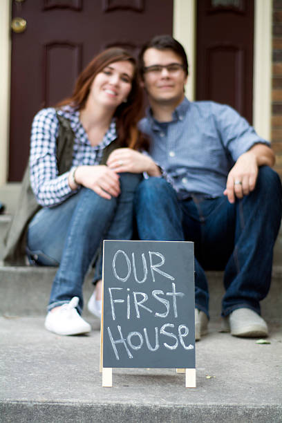 couple on new steps of first home stock photo