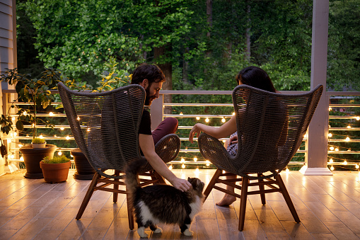 A couple sit in chairs and hold hands on a home patio.  It is early evening, and some string lights on the patio railing are on.  They are facing away from the camera looking out into some trees beyond the patio.  The man is petting a cat that is beside them.  They are relaxing together after a long day.  Shot during the covid-19 related isolation, this is the only place they can go out to relax.  The man is caucasian, the woman is Iranian ethnicity.