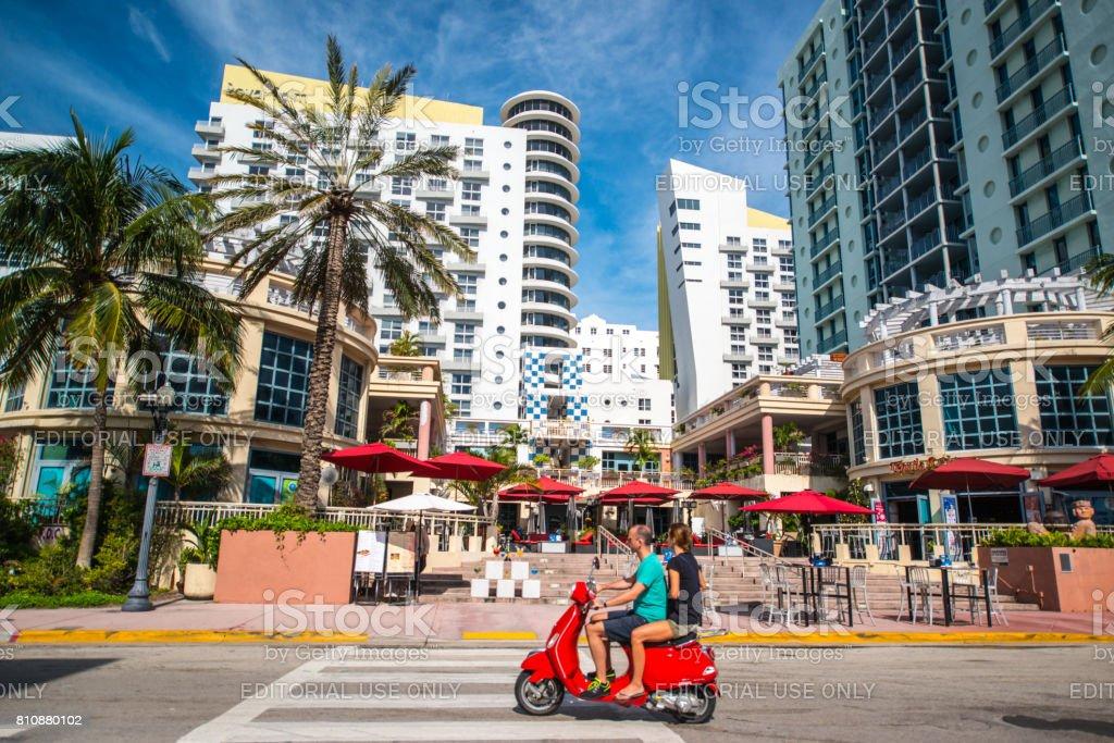 Couple on red Vespa driving on South Beach, Miami Beach, USA stock photo
