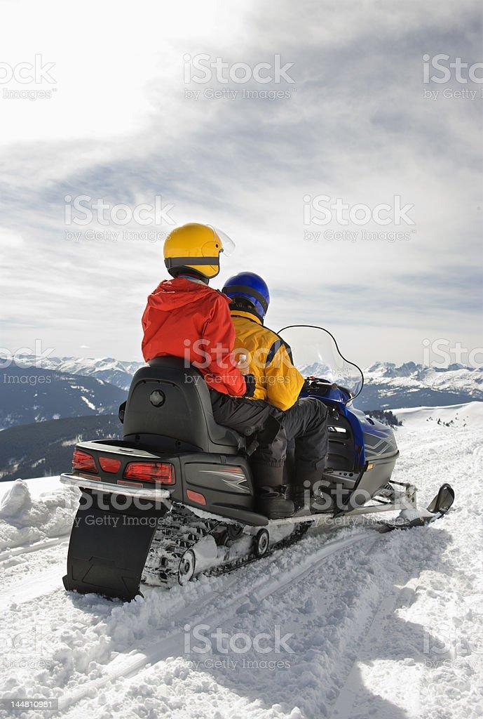 Couple on snowmobile. stock photo