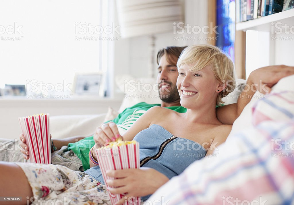 Couple on sofa eating popcorn and watching TV royalty-free stock photo
