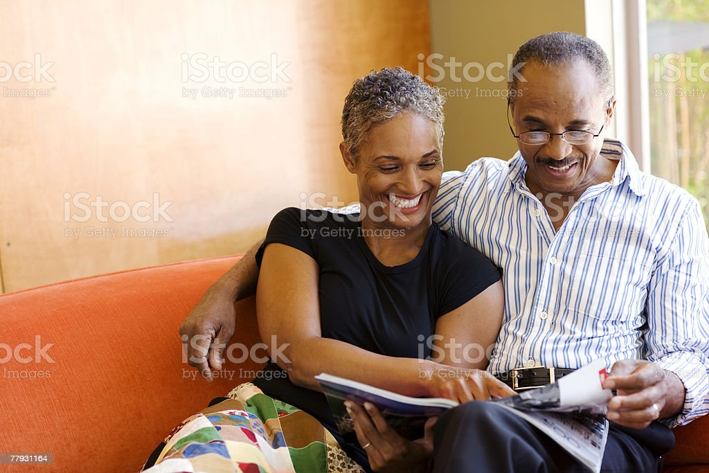 Couple on sofa in modern home with magazine stock photo