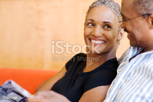 istock Couple on sofa in modern home with magazine 77931165