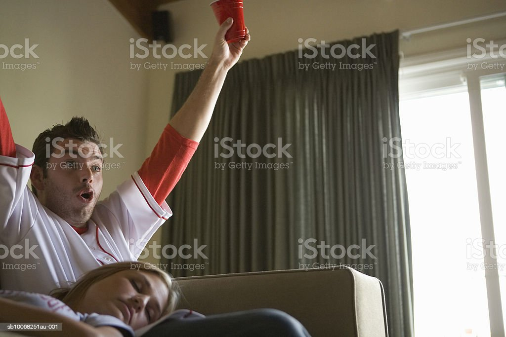 Couple on sofa, man watching tv, woman sleeping royalty free stockfoto