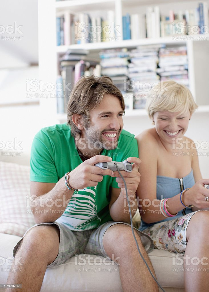 Couple on sofa playing video game royalty-free stock photo