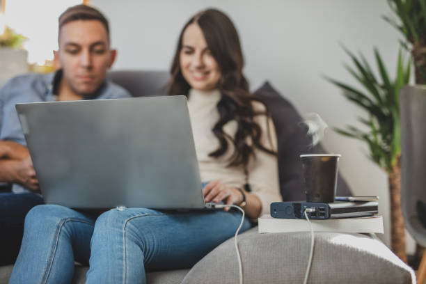 Couple on sofa using laptop plugged into power bank stock photo