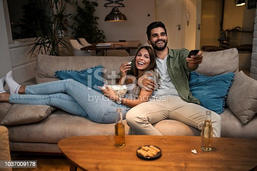 istock Couple on Sofa Watching TV 1037009178