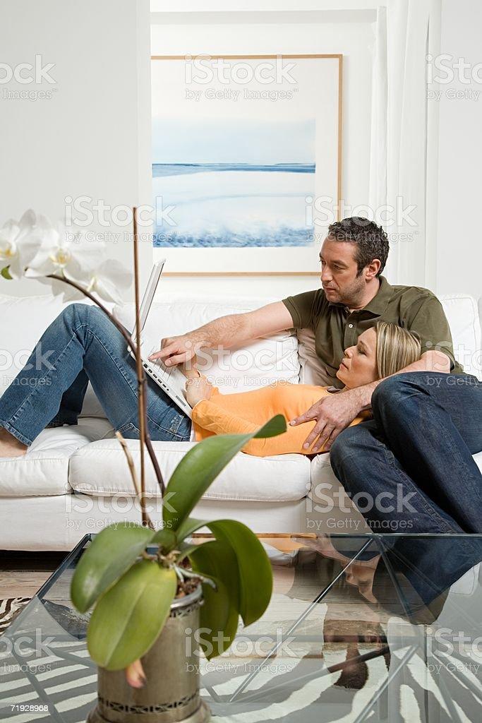 Casal no sofá com o portátil foto de stock royalty-free