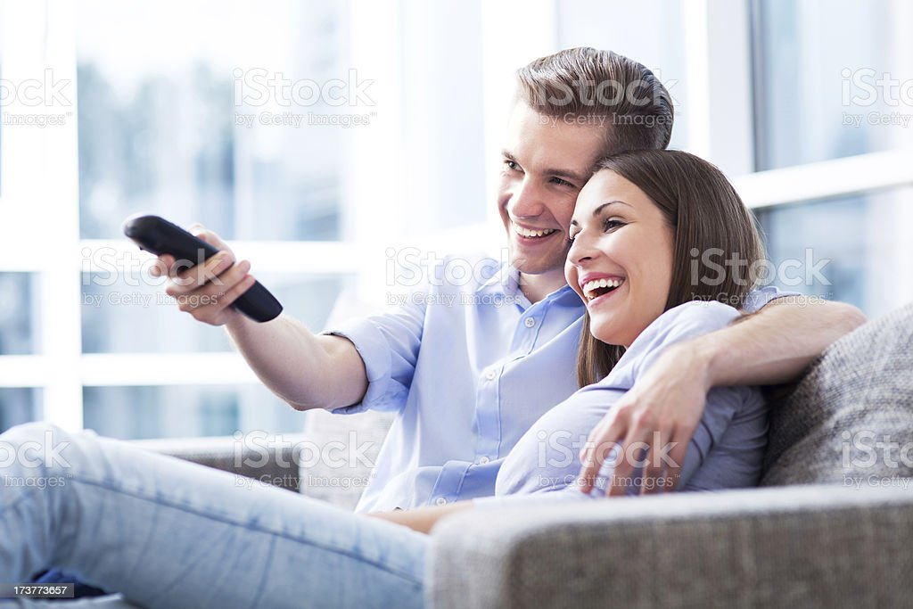 Couple on sofa with TV remote stock photo