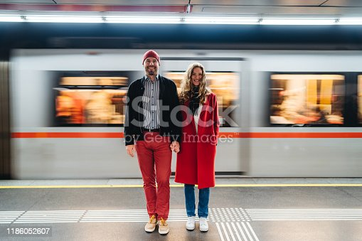 Young Caucasian fashionable couple on subway station.