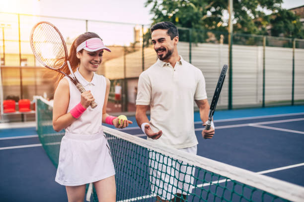 couple on tennis court. - tennis stock pictures, royalty-free photos & images