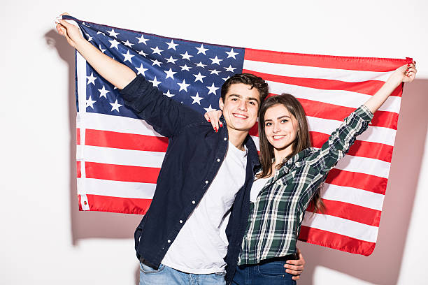 couple on the background of the US flag Portrait of a young happy couple on the background of the US flag green card stock pictures, royalty-free photos & images