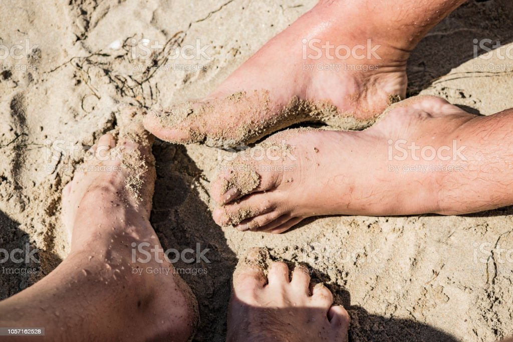 Couple in love on the beach. Close up legs image