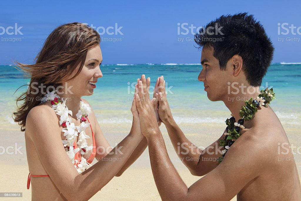 couple on the beach in hawaii touching hands royalty-free stock photo