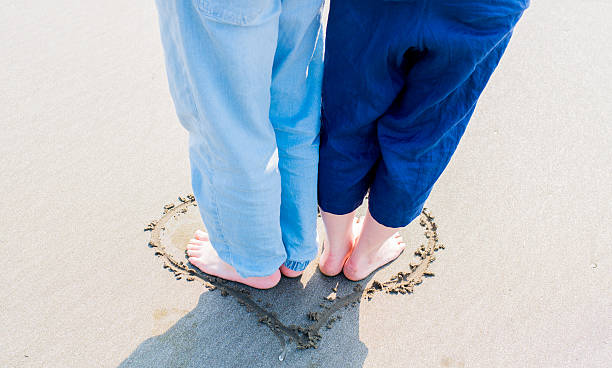 Couple on the beach Couple on the beach. symbiotic relationship stock pictures, royalty-free photos & images