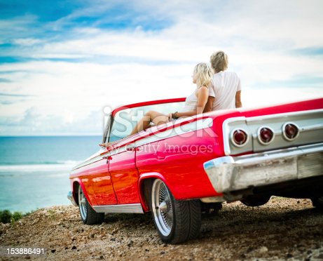 Young couple sitting in the retro car