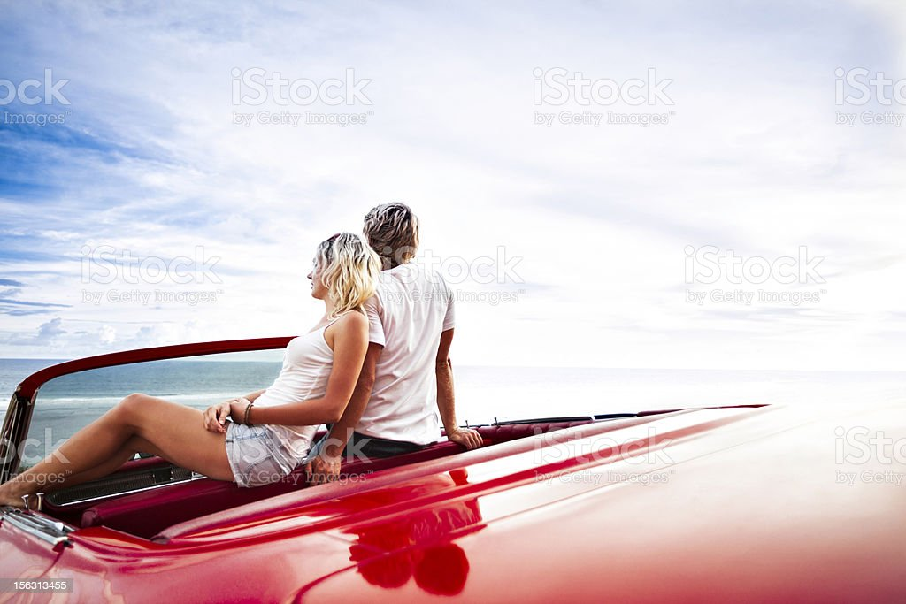 Couple on the cliff sitting in car stock photo