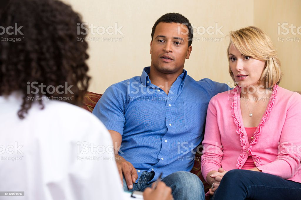 Couple on the couch looking at doctor stock photo