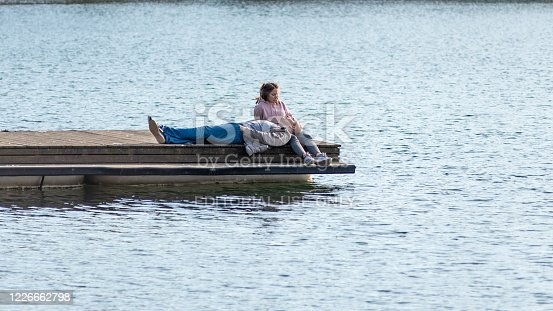 Moscow, Russia, March 28, 2020 - A couple on the pier of boats on the pond, the guy licks putting gold on the girl's lap