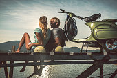 Romantic couple with retro bike on vacation watching sunset