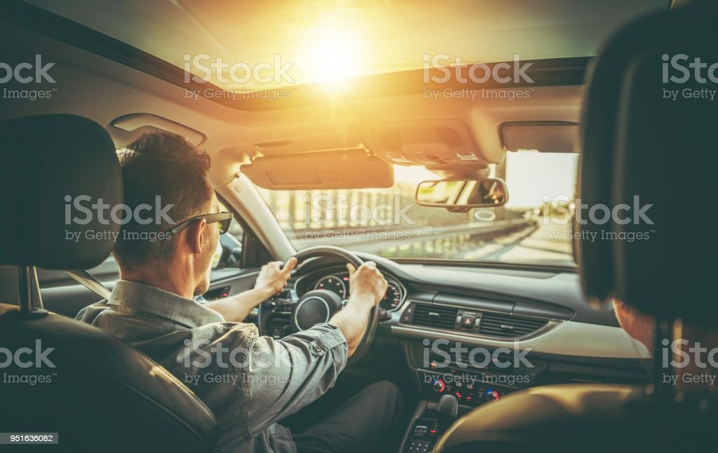 Couple on the Road Trip Caucasian Couple on the Road Trip in the Modern Vehicle with Large Sunroof. Adult Stock Photo