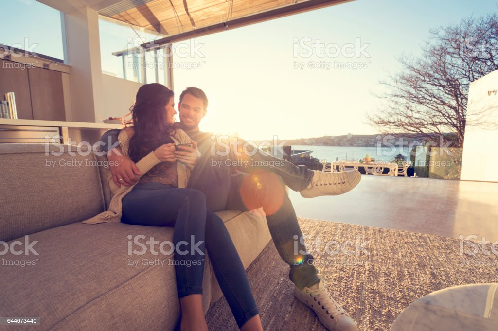 Couple on the sofa at sunrise. stock photo