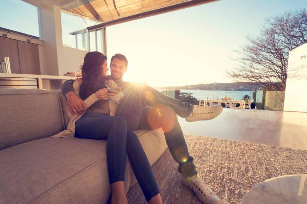 Couple on the sofa at sunrise. stock photo