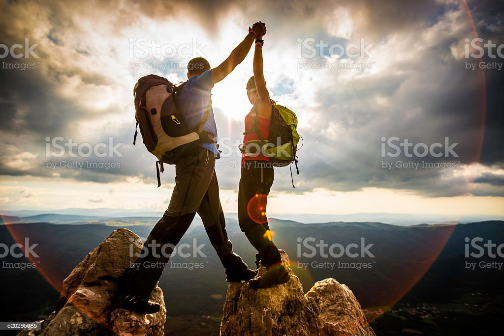 Couple on Top of a Mountain Shaking Raised Hands royalty-free stock photo