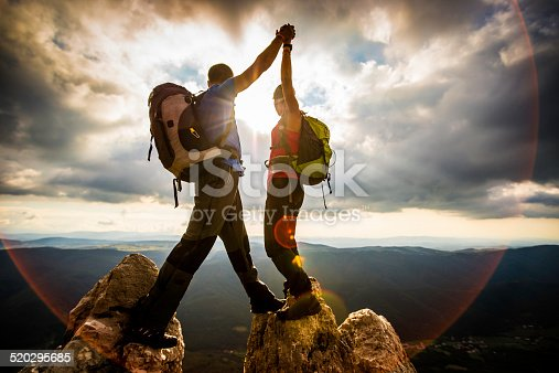 istock Couple on Top of a Mountain Shaking Raised Hands 520295685