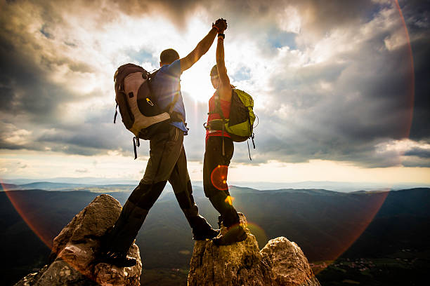 Couple on Top of a Mountain Shaking Raised Hands stock photo