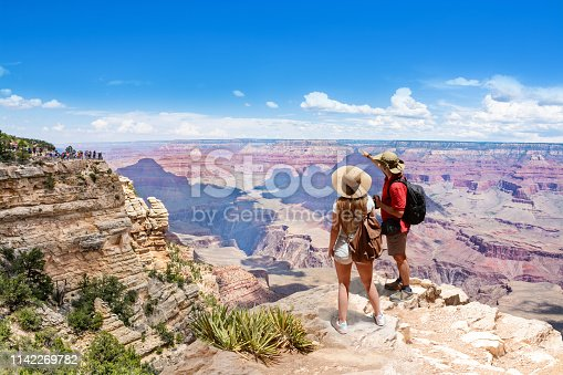 Couple on top of the mountain, looking at beautiful summer mountain  landscape. Friends on hiking trip enjoying view of Colorado river. South Rim. Grand Canyon National Park, Arizona, USA.