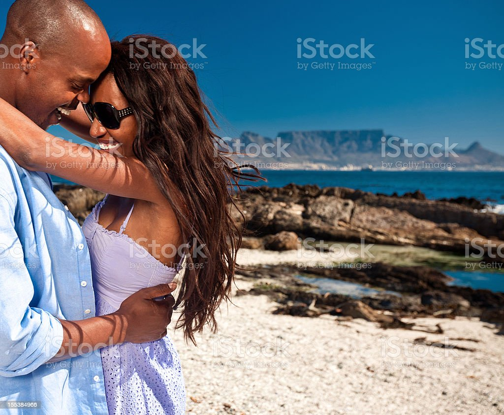 Couple on vacations Romantic african american couple enjoying their summer vacations, embracing against the Table Mountain in the background. Adult Stock Photo